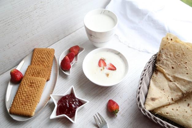 La vista superiore del porridge del riso con latte e gli strawbwrries è servito con inceppamento e biscotti su bianco