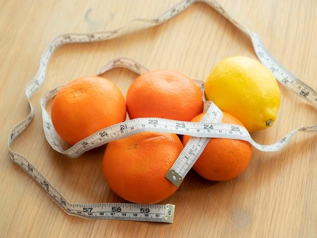La vista superiore dell'arancia, del limone, del nastro di misurazione illustra al prodotto naturale per la dieta di perdita di peso