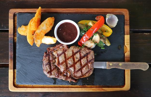 La vista superiore della bistecca alla griglia di ribeye con la salsa del vino rosso è servito sul piatto di pietra caldo