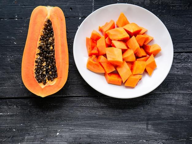 La vista superiore della frutta matura della papaia della fetta a metà e pezzi in piatto bianco su fondo di legno nero.