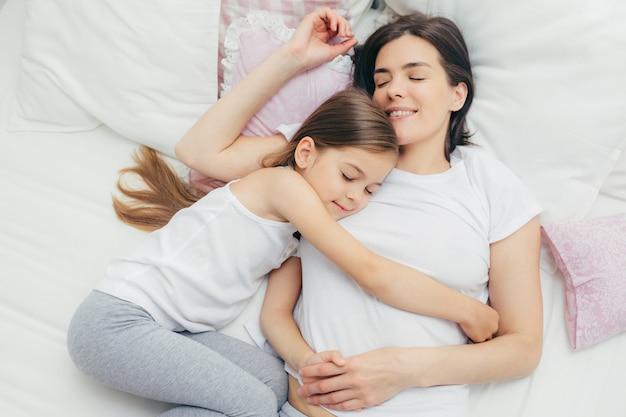 La vista superiore della madre allegra dorme sul letto bianco vicino a sua figlia che abbraccia la mamma con grande amore