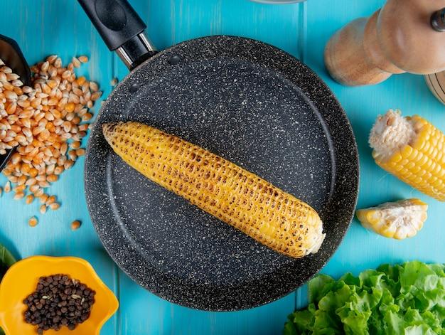 La vista superiore della pannocchia di granturco in pentola con i semi del pepe nero dei semi del mais ha tagliato il mais e la lattuga intorno sulla superficie del blu