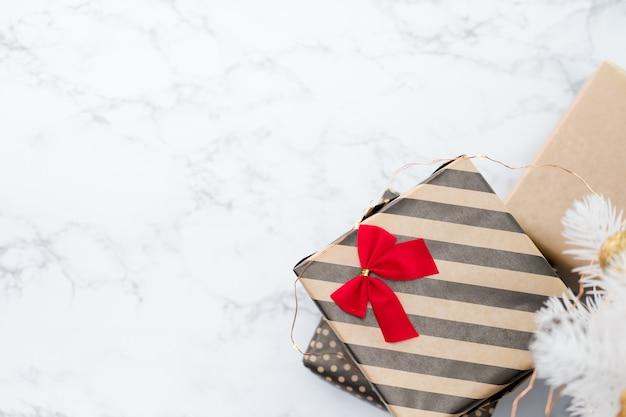 La vista superiore della scatola attuale a strisce moderna con l'arco rosso risiede sotto l'albero di natale bianco sul pavimento di marmo bianco