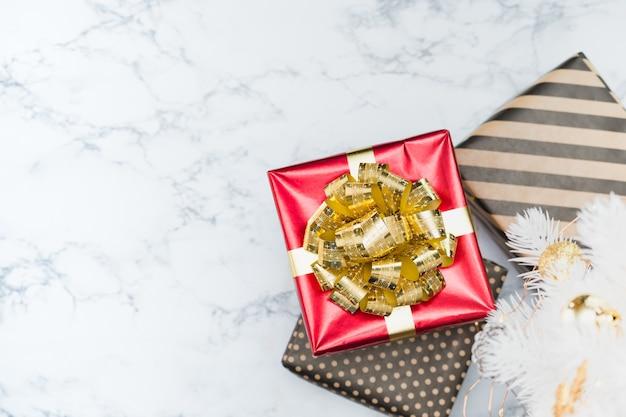 La vista superiore della scatola attuale lucida rossa con l'arco ed il nastro dorati risiede sotto l'albero di natale bianco sul pavimento di marmo bianco