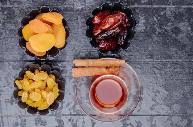 La vista superiore delle albicocche secche dell'uva passa e dei datteri secchi in mini scatole di latta servite con tè su fondo di legno nero