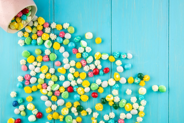 La vista superiore delle caramelle di zucchero dolci variopinte ha sparso da una ciotola su fondo di legno blu