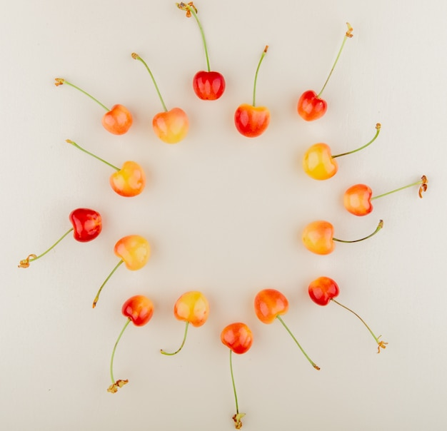La vista superiore delle ciliege rosse e gialle ha messo nella forma rotonda su bianco