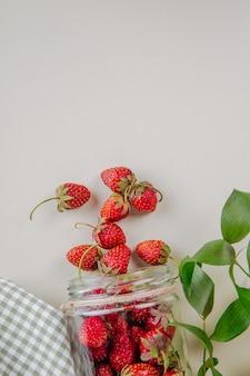 La vista superiore delle fragole mature fresche ha sparso dal barattolo di vetro su bianco