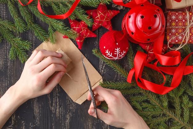 La vista superiore delle mani del bambino avvolge il presente di nuovo anno