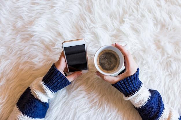 La vista superiore delle mani della donna che tengono uno smart phone sopra fondo bianco. tazza di caffè e stili di vita.