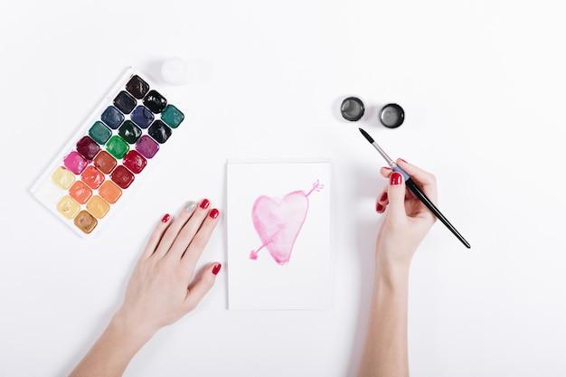 La vista superiore delle mani di una femmina con il manicure rosso disegna il cuore dell'acquerello in taccuino