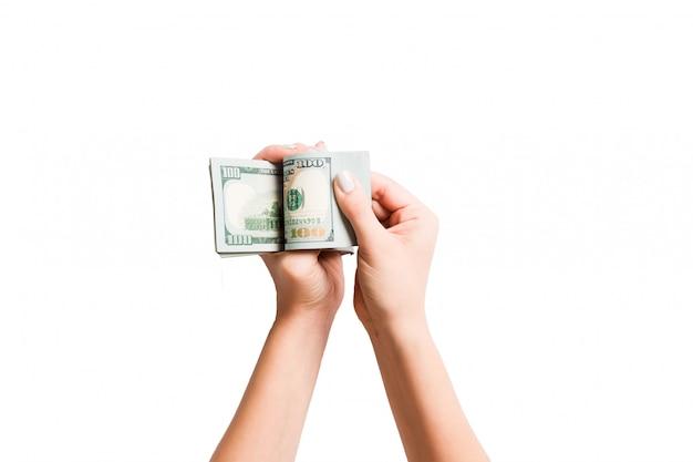 La vista superiore delle mani femminili che contano le banconote del dollaro su bianco ha isolato il fondo