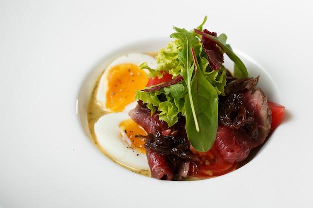 La vista superiore delle uova del piatto con incontra e insalata sul piatto