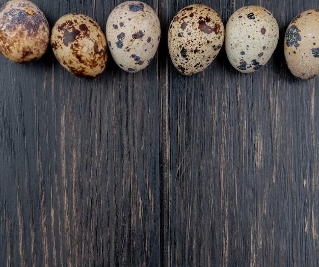 La vista superiore delle uova di quaglia con le coperture color crema ha sistemato in una linea su un fondo di legno con lo spazio della copia