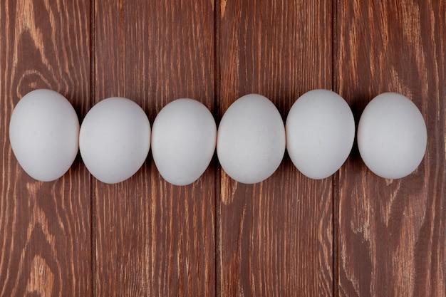 La vista superiore delle uova fresche bianche del pollo ha sistemato in linea su un fondo di legno