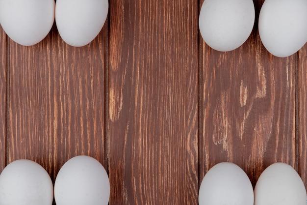 La vista superiore delle uova fresche bianche del pollo ha sistemato nei lati differenti su un fondo di legno con lo spazio della copia