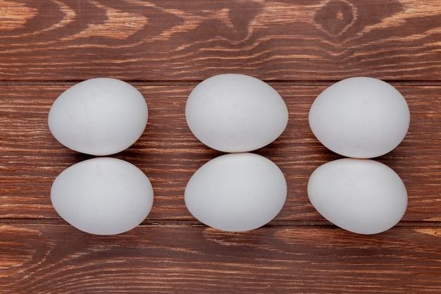 La vista superiore delle uova fresche bianche del pollo ha sistemato su un fondo di legno