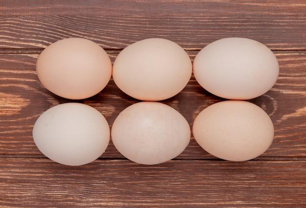 La vista superiore delle uova fresche del pollo ha sistemato la linea su un fondo di legno