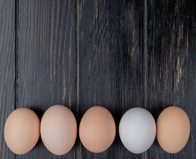La vista superiore delle uova fresche del pollo sopra ha sistemato in una linea su un fondo di legno con lo spazio della copia