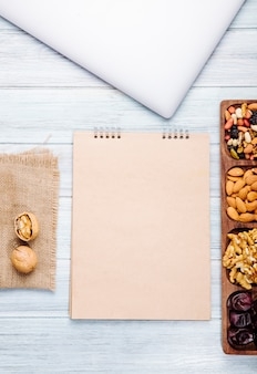 La vista superiore dello sketchbook e dei dadi si mescola con la mandorla delle noci e la frutta secca dolce del dattero su di legno