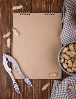La vista superiore dello sketchbook e una ciotola hanno riempito di arachidi in cracker del dado e delle coperture su fondo di legno
