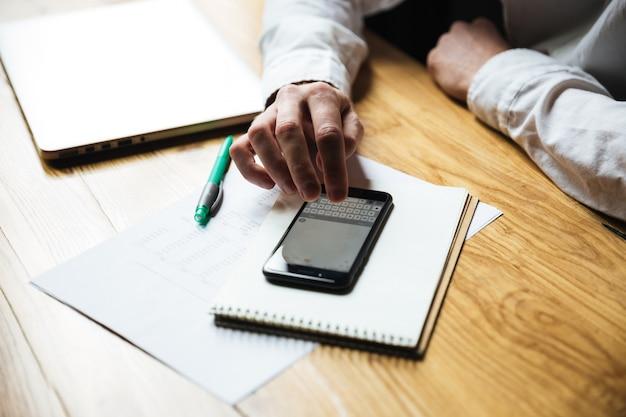 La vista superiore di equipaggia il messaggio mandante un sms della mano sullo smartphone