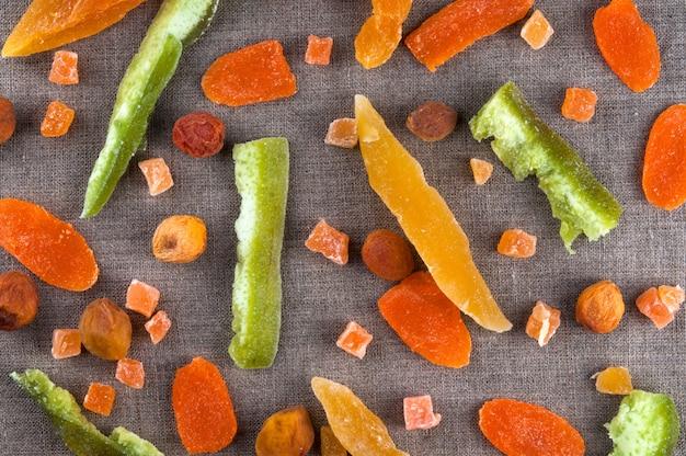 La vista superiore di frutti e di zucchini variopinti secchi sani taglia sul fondo di tela grigio del panno del tessuto