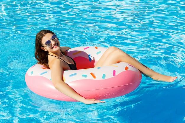 La vista superiore di giovane femmina nuota con il cerchio rosa in stagno