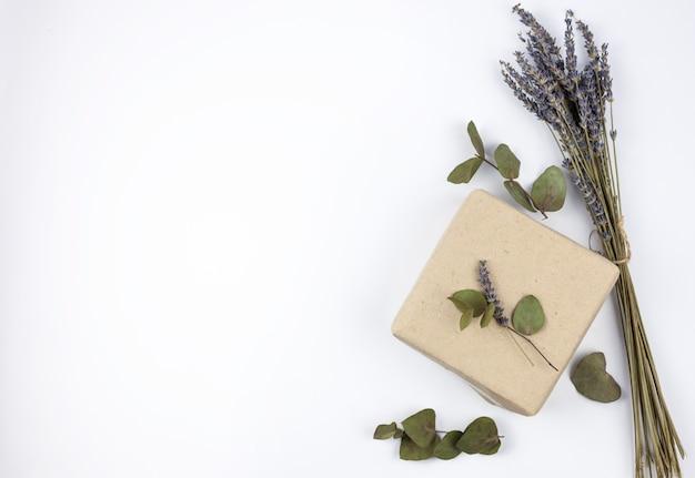 La vista superiore di lavanda fiorisce con il contenitore di regalo marrone contro isolato su fondo bianco