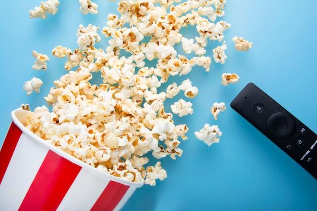 La vista superiore di popcorn rovesciato su un fondo blu con la tv rimuove
