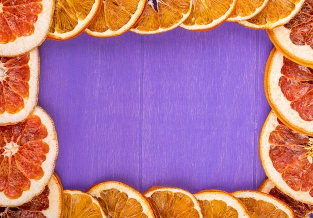 La vista superiore di una struttura fatta delle fette secche di arancia e di pompelmo ha sistemato su fondo di legno porpora con lo spazio della copia