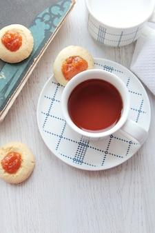 La vista superiore di una tazza di tè nero è servito con i biscotti con inceppamento