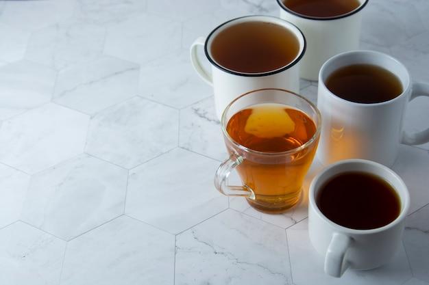 La vista superiore di varie tazze, tazze con tè caldo beve su luce, copyspace. ora del tè o freno del tè. bevanda autunnale. immagine tonica con tazze da tè.