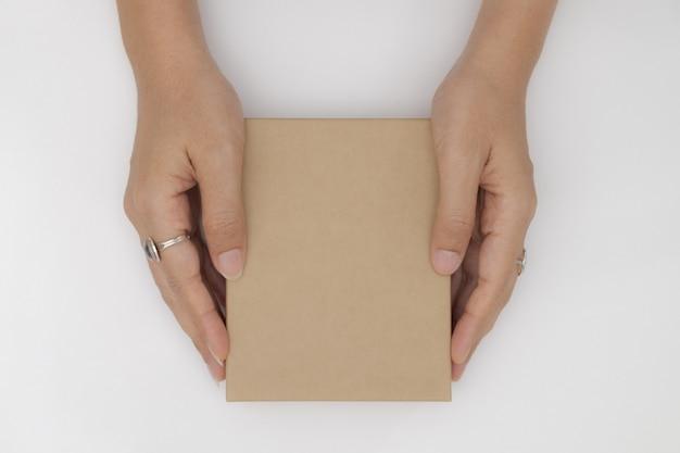 La vista superiore due mani che tengono e aprono il fondo bianco isolato contenitore di regalo vuoto