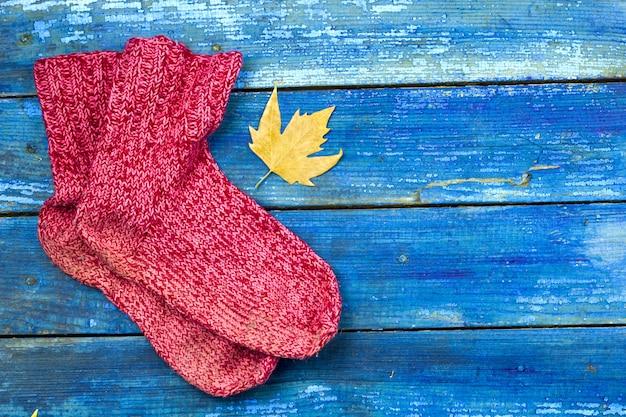La vista superiore ha rted i calzini lavorati a maglia, foglie gialle di autunno sui bordi di legno blu