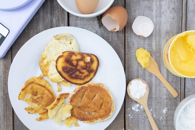 La vista superiore, pancake bruciato sul piatto bianco a fondo di legno, alimento non può mangiare concetto.