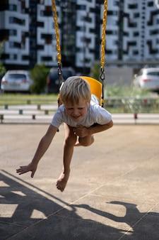 La vita dei bambini in una città moderna - il ragazzino si diverte nel parco giochi vicino alla casa