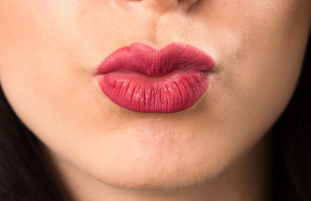 Labbra della giovane donna che manda un bacio
