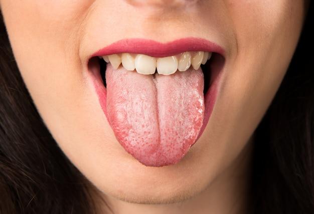 Labbra della giovane donna tirando fuori la lingua