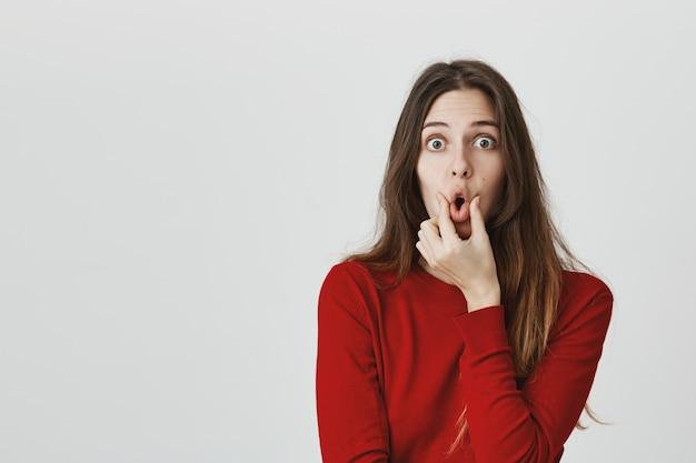 Labbra divertenti di compressione della ragazza che fanno sopra la bocca e la macchina fotografica di sguardo