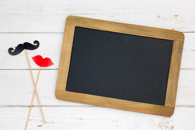 Labbra e baffi e lavagna falsi di forma di cuore di carta su fondo bianco di legno.