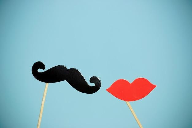 Labbra e baffi finti di forma di cuore di carta in bastoni davanti a fondo blu.