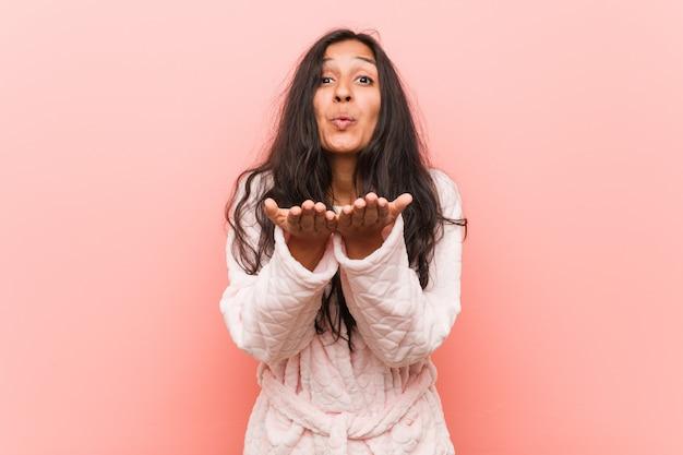 Labbra pieganti da portare del pigiama della giovane donna indiana e tenere le palme per inviare bacio dell'aria.