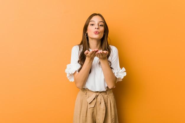 Labbra pieganti della giovane donna caucasica e tenere le palme per inviare bacio dell'aria.