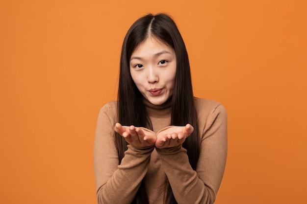Labbra pieganti della giovane donna graziosa cinese e tenere le palme per inviare bacio dell'aria