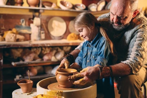 Laboratorio di ceramica. il nonno insegna ceramica nipote. modellazione di argilla
