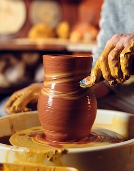 Laboratorio di ceramica. un uomo anziano fa un vaso di argilla. modellazione di argilla