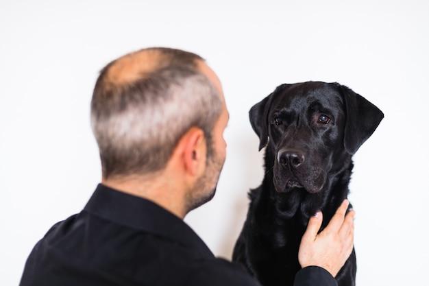 Labrador nero e il suo proprietario a casa. concetto di amicizia. uomo che accarezza il suo cane