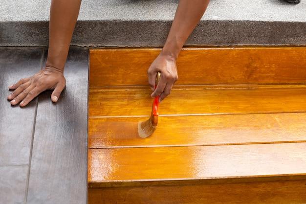 Lacca di verniciatura del lavoratore sul pavimento di legno all'aperto dal pennello.