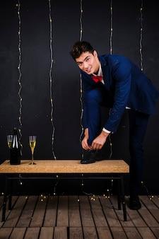 Lacci delle scarpe di fissaggio del giovane vicino a vetro e bottiglia di champagne